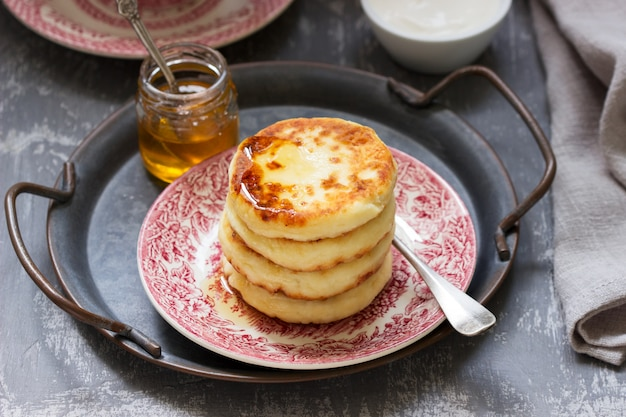 Cottage cheese pancakes, homemade syrniki with honey and sour cream.