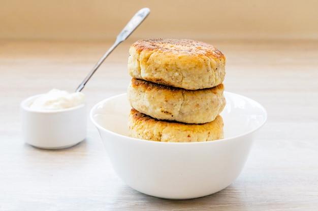白い木製のテーブルにサワークリームと丸い白いボウルのカッテージチーズのパンケーキ