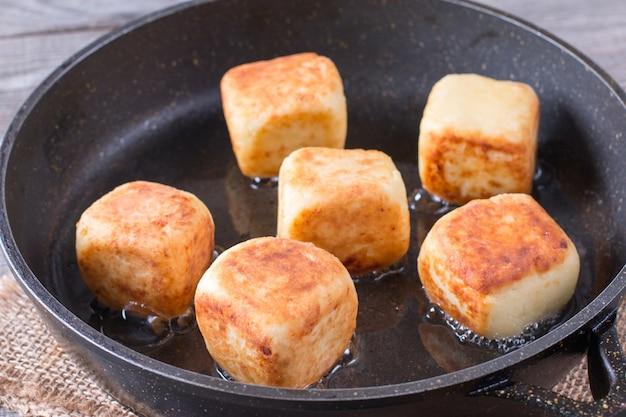 Творожные оладьи в виде кубиков на сковороде