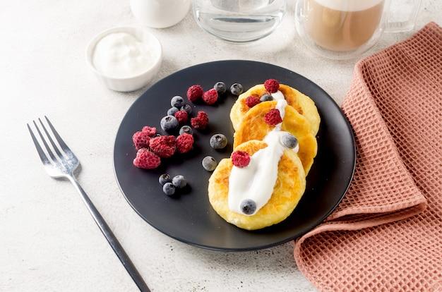 ベリー、クリーム、ジャム、ラテのカップと黒いプレート上のカッテージチーズのパンケーキ。健康的な朝食。手作りの料理