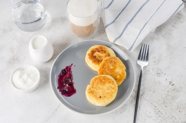 クリーム、ジャム、ラテのカップと黒いプレート上のカッテージチーズのパンケーキ。健康的な朝食。手作りの料理