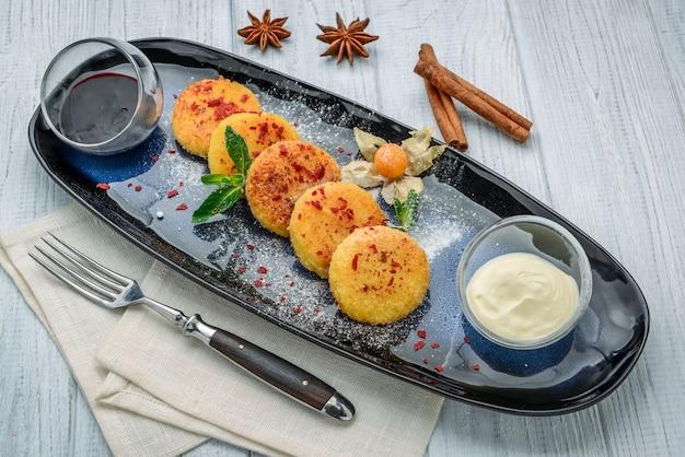 皿の上のカッテージチーズのパンケーキ。健康的でダイエットの朝食。木製のテーブルの上