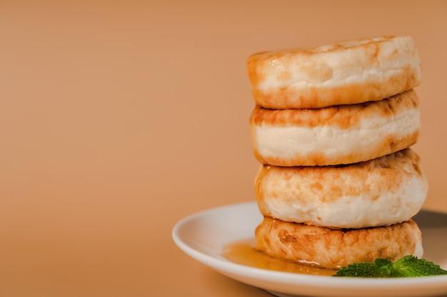 Творожные оладьи на тарелке с медом и мятойполезно и вкусно