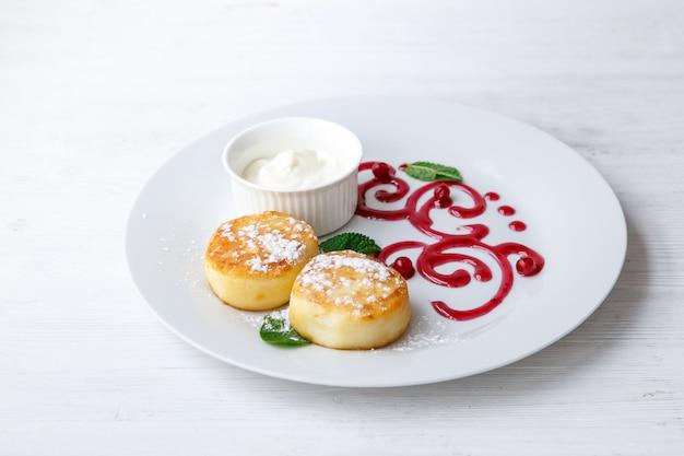 Сырники или творожки со сметаной на белой керамической тарелке украшены джемом. вкусный завтрак или бранч. меню