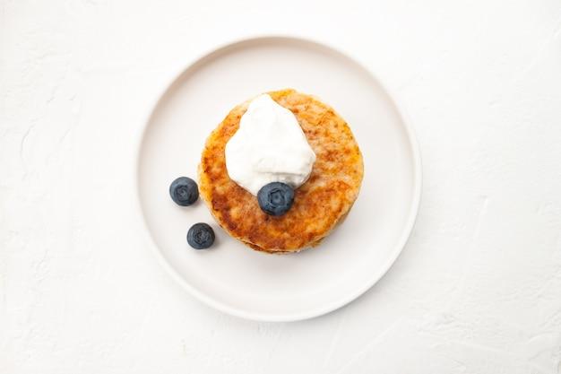 カッテージチーズのパンケーキまたは豆腐のフリッターは、白いプレートのクローズアップビューでサワークリームとアーモンドのブルーベリーとココナッツフラワーグルテンフリーとスタックします。健康的な朝食を食べる。選択的なソフトフォーカス。