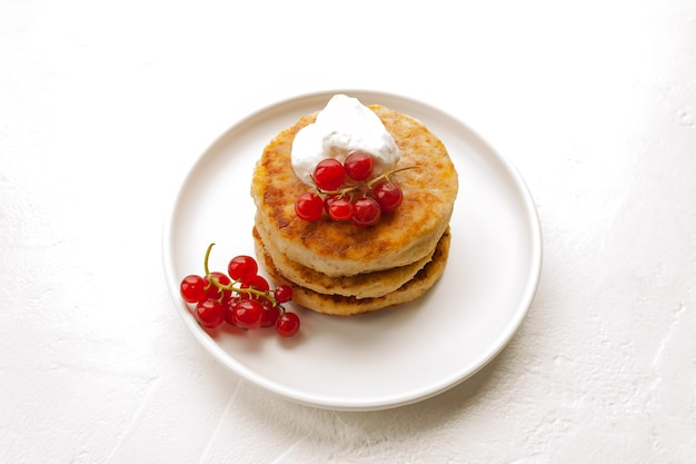 カッテージチーズのパンケーキまたは豆腐のフリッターは、白いプレートのクローズアップビューでサワークリームとアーモンドとココナッツフラワーグルテンフリーの赤スグリとスタックします。健康的な朝食を食べる。選択的なソフトフォーカス。