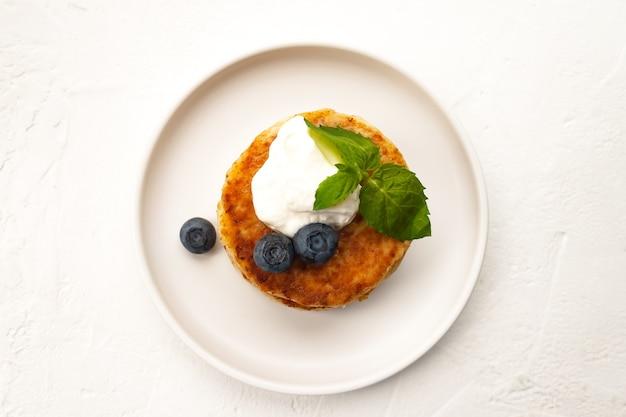 Творожные оладьи или творожные оладьи складываются со сметаной, мятой, черникой из миндаля и без глютена кокосовой муки в белой тарелке крупным планом. здоровый завтрак. селективный мягкий фокус