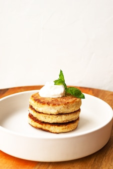 カッテージチーズのパンケーキまたは豆腐のフリッターは、白いプレートのクローズアップビューでアーモンドとココナッツフラワーグルテンフリーで飾られたサワークリームミントとスタックします。健康的な朝食を食べる。選択的なソフトフォーカス。
