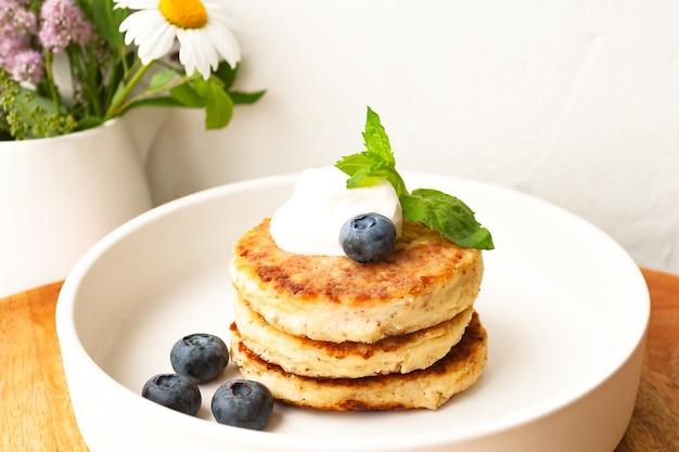 カッテージチーズのパンケーキまたは豆腐のフリッターは、サワークリーム、ミントの葉、アーモンドのブルーベリー、白いプレートにグルテンフリーのココナッツ粉を重ねたものです。健康的な朝食を食べる。セレクティブフォーカス。