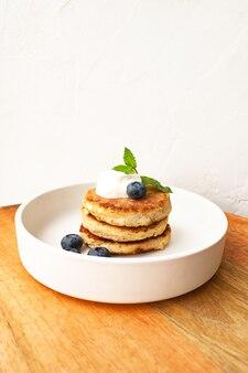 Творожные оладьи или творожные оладьи складываются со сметаной, листом мяты и черникой миндаля и без глютена кокосовой муки в белой тарелке крупным планом. концепция завтрака. селективный мягкий фокус.