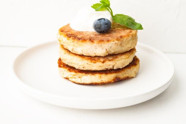 カッテージチーズのパンケーキまたは豆腐のフリッターは、サワークリーム、ミントの葉、アーモンドのブルーベリー、白いプレートにグルテンフリーのココナッツ粉を重ねたものです。朝食のコンセプト。選択的なソフトフォーカス。