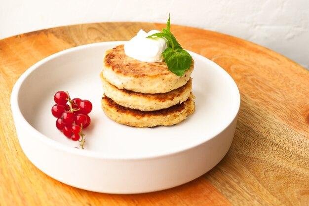 カッテージチーズのパンケーキまたは豆腐のフリッターは、サワークリーム、ミントの葉、アーモンドとココナッツ粉のグルテンフリーの赤スグリが白いプレートに積み重ねられています。健康的な朝食を食べる。セレクティブフォーカス。