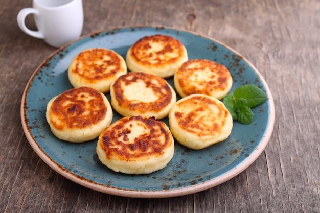 Творожные оладьи или сырники на голубой тарелке, украшенные мятой, крупным планом. русская, украинская кухня. здоровый вкусный завтрак.