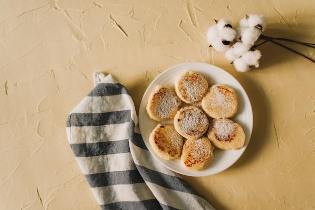 カッテージチーズのパンケーキまたはシルニキとセラミックプレートで美味しい朝食またはブランチ