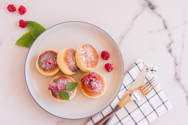 라즈베리와 설탕 가루를 곁들인 코티지 치즈 팬케이크 또는 시르니키. 건강한 아침 식사. 프리미엄 사진