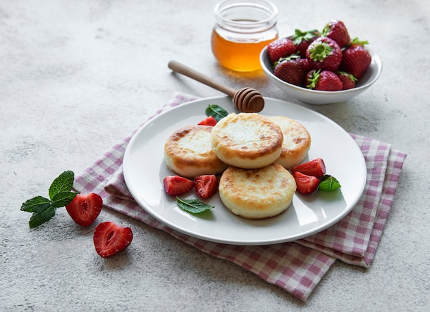 Cottage cheese pancakes, ricotta fritters on ceramic plate with  fresh strawberry. healthy and delicious morning breakfast.  grey concrete background.