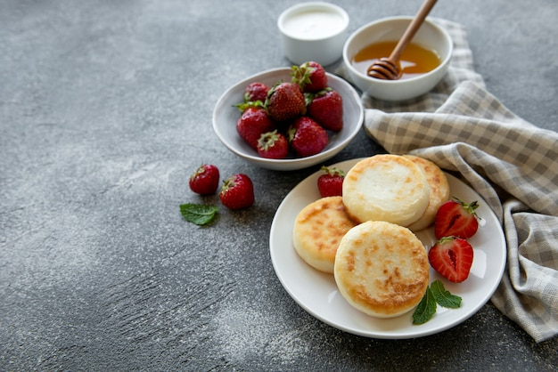 Cottage cheese pancakes, ricotta fritters on ceramic plate with  fresh strawberry. healthy and delicious morning breakfast.
