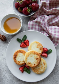 Cottage cheese pancakes ricotta fritters on ceramic plate with  fresh strawberry