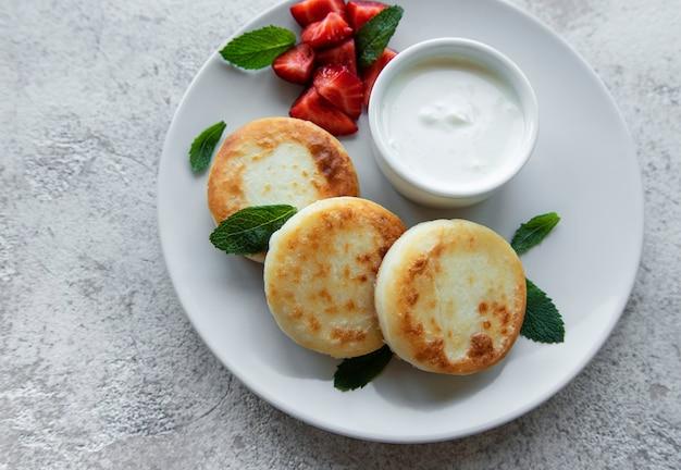 Творожные оладьи, оладьи из рикотты на керамической тарелке со свежей клубникой. здоровый и вкусный утренний завтрак. серый бетонный фон.