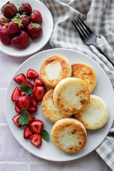 코티지 치즈 팬케이크, 신선한 딸기와 세라믹 접시에 리코타 튀김. 건강하고 맛있는 아침식사. 회색 콘크리트 배경입니다.