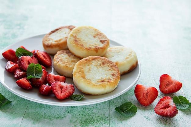 Творожные оладьи, оладьи из рикотты на керамической тарелке со свежей клубникой. здоровый и вкусный утренний завтрак.
