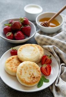 코티지 치즈 팬케이크, 신선한 딸기와 세라믹 접시에 리코타 튀김. 건강하고 맛있는 아침식사.