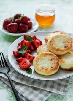 カッテージチーズのパンケーキリコッタフリッターと新鮮なイチゴのセラミックプレート