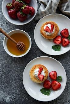 신선한 딸기와 함께 세라믹 접시에 코티지 치즈 팬케이크 리코타 튀김
