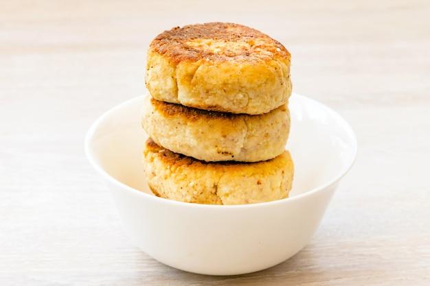 カッテージチーズのパンケーキは、白い木製のテーブルの上の丸い白いボウルにスタックします