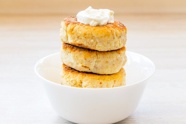 Cottage cheese pancakes stack in round white bowl with sour cream on white wooden table