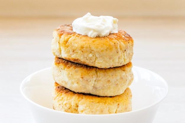 カッテージチーズのパンケーキは、白い木製のテーブルの上の丸い白いボウルにサワークリームとスタックします。