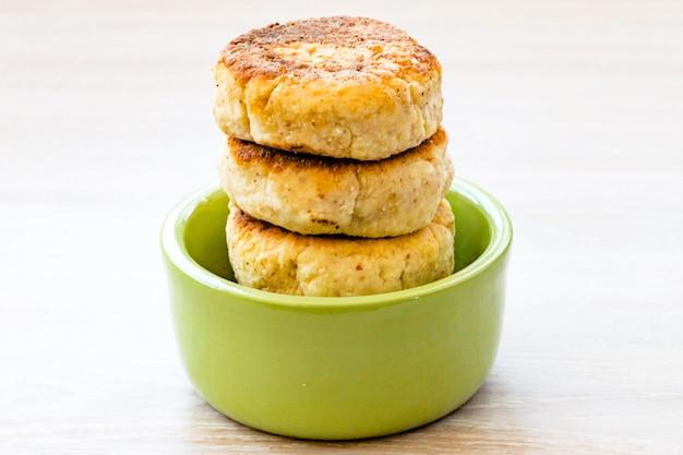 白い木製のテーブルの上の丸い緑のボウルに積み重ねられたカッテージチーズのパンケーキ