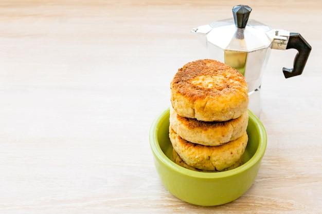 間欠泉コーヒーメーカーと丸い緑のボウルに積み重ねられたカッテージチーズのパンケーキ