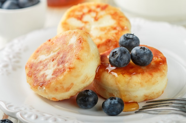 Cottage cheese pancakes, syrniki, curd fritters with fresh berries blueberry and honey in a white plate, gourmet breakfast