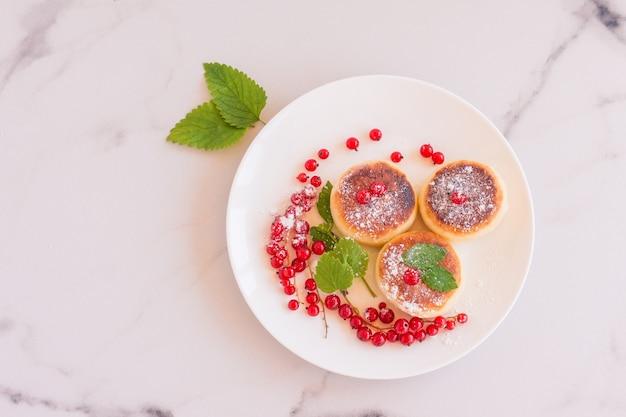 코티지 치즈 팬케이크, 시르니키, 하얀 접시에 붉은 건포도의 신선한 딸기가 있는 두부 튀김. 미식가 아침 식사. 선택적 초점