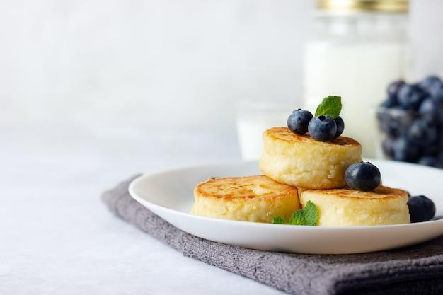 Творожные оладьи, сырники, творожные оладьи со свежей черникой и молоком на светлом фоне. скопируйте место для вашего текста. русское меню завтрака.