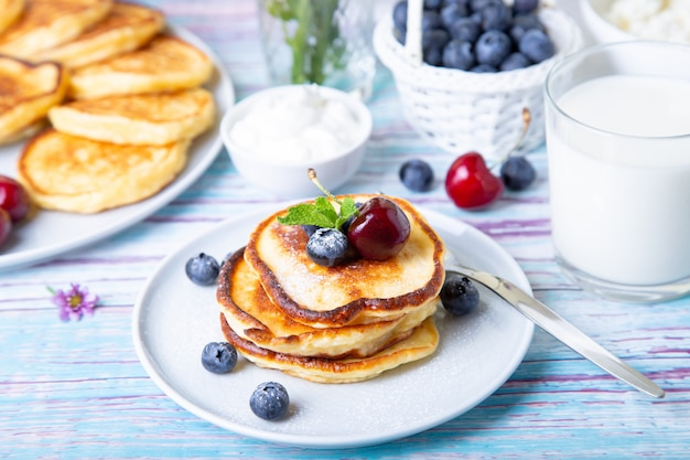 Cottage cheese pancakes (syrniki). homemade cheesecakes from cottage cheese with sour cream, berries and milk. traditional russian dish. close-up.