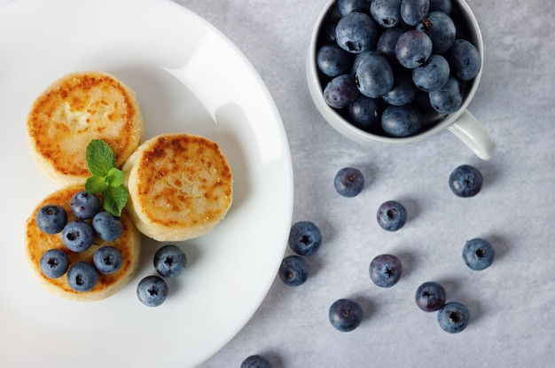 カッテージチーズのパンケーキ、白いプレートにブルーベリーを添えたシルニキ。