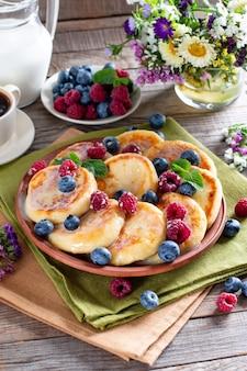 Творожные оладьи, сырники с черникой в тарелке, завтрак или обед