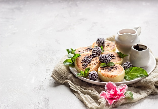 Cottage cheese pancakes with berries, chocolate and mint. syrniki. gourmet breakfast.