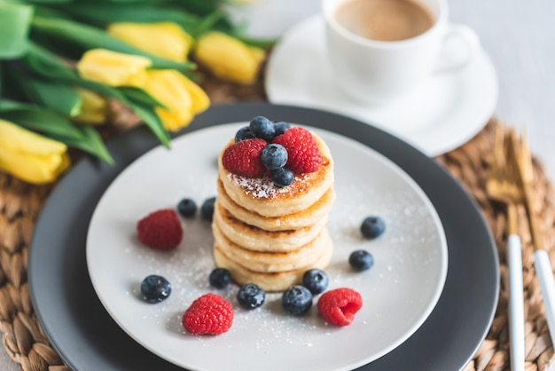Cottage cheese pancakes with berries and coffee