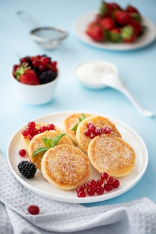 Cottage cheese pancakes with berries and sour cream on a blue table