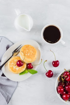 Cottage cheese pancakes with berry cherry, cup of black coffee, milk