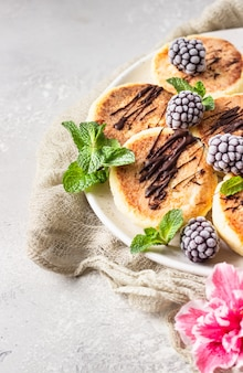 Cottage cheese pancakes with blackberries, chocolate and mint. syrniki. gourmet breakfast.