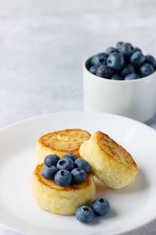 블루 베리, 건강한 아침 식사와 코티지 치즈 팬케이크. 러시아, 우크라이나 요리 음식.