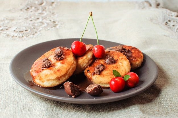 Cottage cheese pancakes with cherries and chocolate in a brown plate.