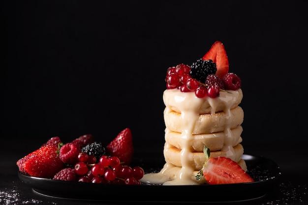 Творожные оладьи со свежими ягодами и сгущенкой на черном блюде