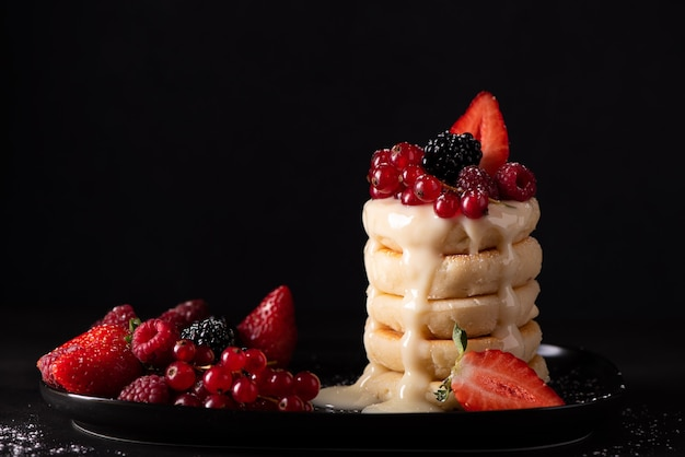 Cottage cheese pancakes with fresh berries and condensed milk on a black dish