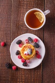 暗い茶色の木製の表面にレモンスライスとホットティーカップの近くのプレートにラズベリーとブラックベリーの果実とカッテージチーズのパンケーキ