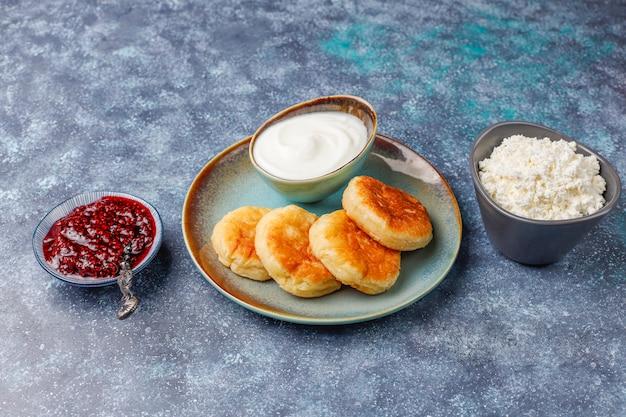 Сырники с малиновым вареньем. русские сырники или сирники, творожные оладьи или блины с миской свежего домашнего творога на темно-сером